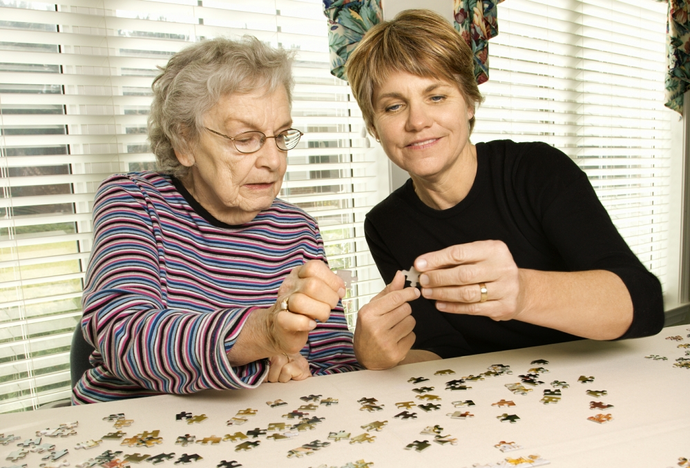 Elderly woman and carer work on a jigsaw puzzle together.